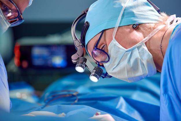Sluit omhoog portret van vrouwelijke chirurg arts die beschermend masker en hoed dragen tijdens de operatie.
