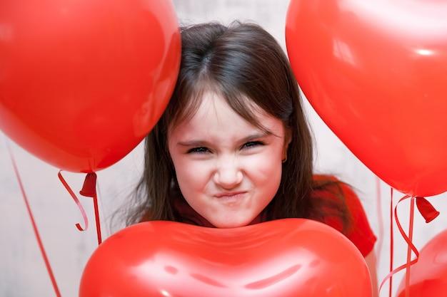 Sluit omhoog portret van weinig ondeugend boos meisjesgezicht dicht omhoog onder rode hartvormige ballons