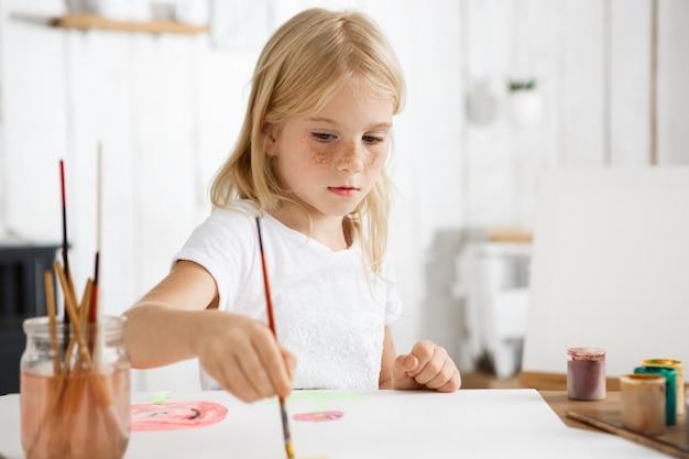 Sluit omhoog portret van weinig wit-gevild meisje met blond haar en sproeten concentreerde zich bij het schilderen van beeld