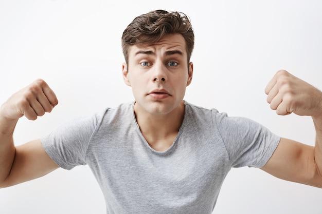 Sluit omhoog portret van zekere jonge kaukasische mannelijke atleet met spierlichaam, aantonend hoe sterk hij is, pronkt van zich. een knappe sporter toont zijn spieren en kracht.