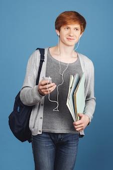 Sluit omhoog portret van zekere vrolijke jonge knappe student met de boeken van de rugzakholding in handen, babbelend op smartphone met vriend, luisterend aan muziek in oortelefoons.