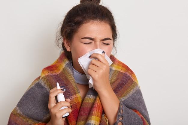 Sluit omhoog portret van zieke vrouw die lopende neus blazen, griep hebben, niezend in zakdoek, het stellen met gesloten ogen gewikkeld geruite plaid die op witte studio wordt geïsoleerd