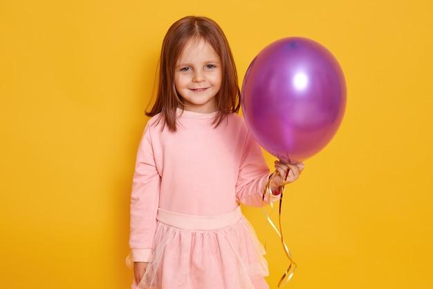 Sluit omhoog portret van zoet aardig meisje met purpere ballon in handen.