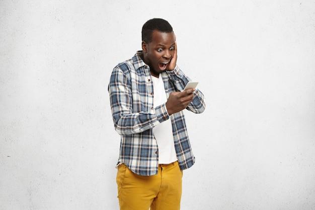 Sluit omhoog portret van zwarte geschokte hipster in modieuze en trendy gele broek, houdend smartphone in één hand wat betreft zijn hoofd