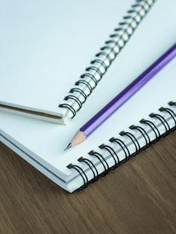 Sluit omhoog potlood en spiraalvormig notitieboekje op houten lijst, selectief nadrukpunt