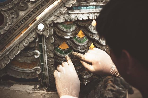 Sluit omhoog pottenbakkerskunstenaar die aan het beeldhouwwerk fijne kunst van het kleiaardewerk in thailand werken