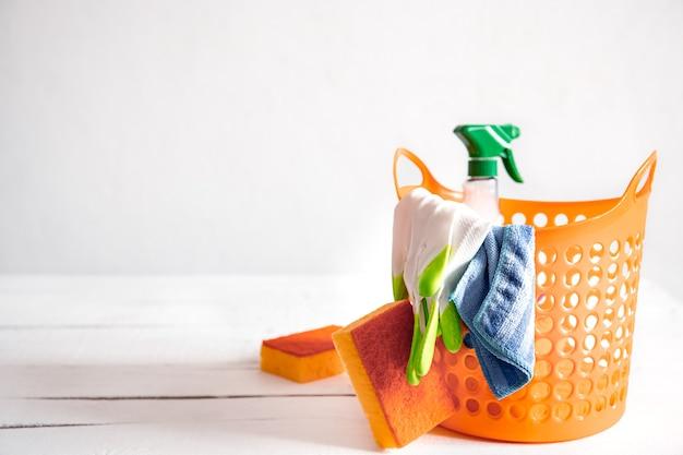 Sluit omhoog reeks huis schoonmakende producten in een heldere mand. middelen voor het handhaven van reinheid achtergrond