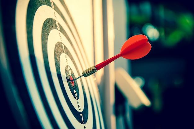 Sluit omhoog rode kleurenpijl in het midden van schot in de roos voor zakelijke targeting en goed succes.