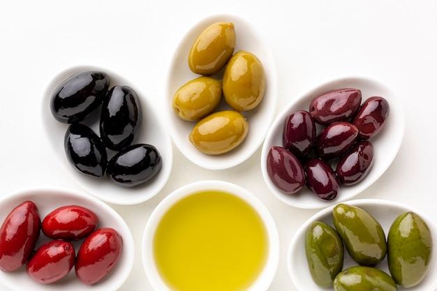 Sluit omhoog rode zwarte gele purpere olijven op platen met bladeren en olijfschotel