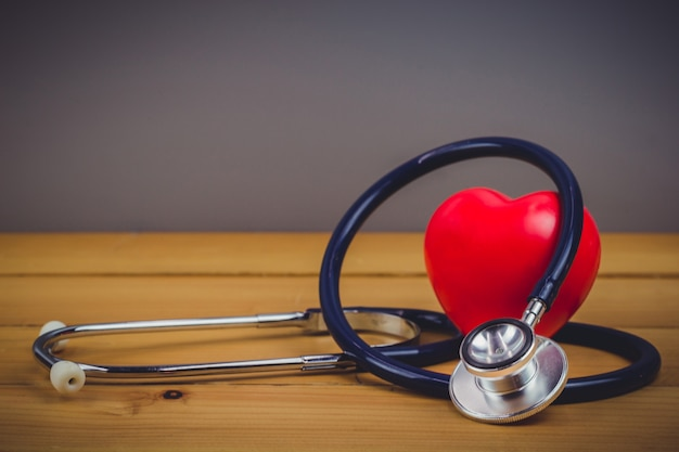 Sluit omhoog rood hart en steythoscope op oude houten lijst
