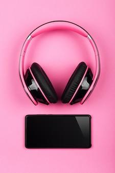 Sluit omhoog roze hoofdtelefoons en mobiele telefoon