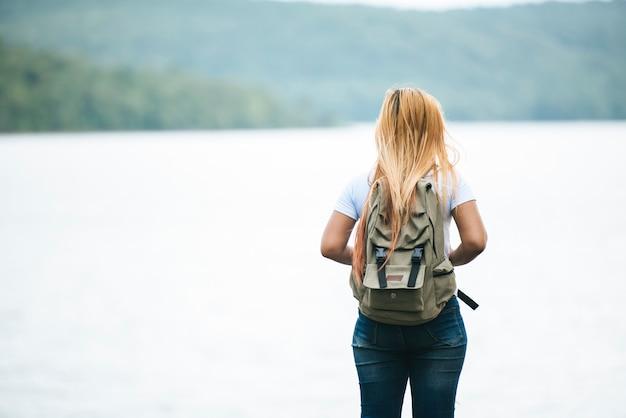 Sluit omhoog rug van toeristenmeisje met wapens opheffen gelukkig met aard dichtbij meer.