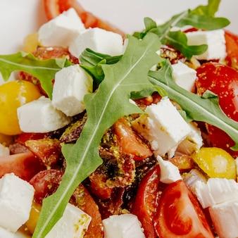 Sluit omhoog salade met feta-kaas, in de zon gedroogde tomaten en rucola
