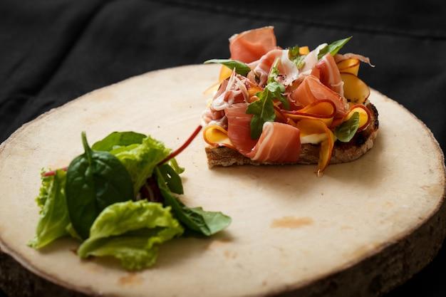Sluit omhoog sandwich met jamon en salade aan boord