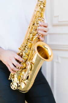 Sluit omhoog saxofoon die door de mens wordt gespeeld