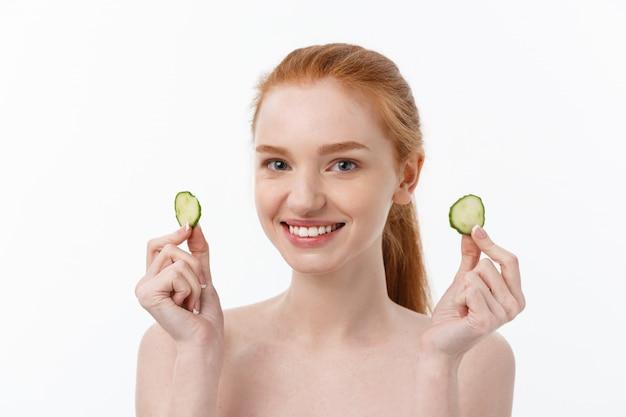 Sluit omhoog schoonheidsportret van een glimlachende mooie half naakte de komkommerplakken van de vrouwenholding bij haar die gezicht over witte achtergrond wordt geïsoleerd