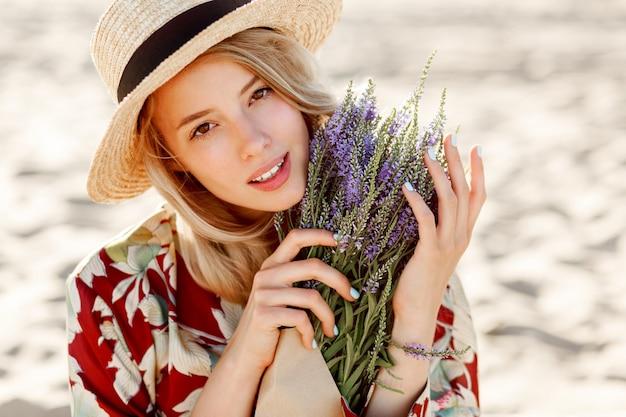 Sluit omhoog schoonheidsportret van mooi romantisch blond meisje die van perfecte geur van lavendel genieten. huidverzorging en cosmetisch concept. warme zonsondergangkleuren.