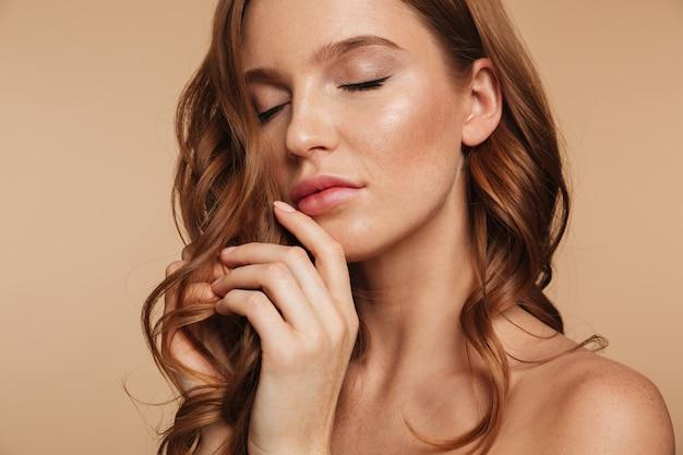 Sluit omhoog schoonheidsportret van sensuele gembervrouw met het lange haar stellen met gesloten ogen