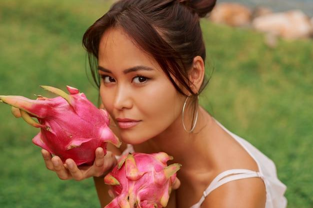 Sluit omhoog schoonheidsportret van vrij aziatische vrouw met draakfruit naast gezicht.