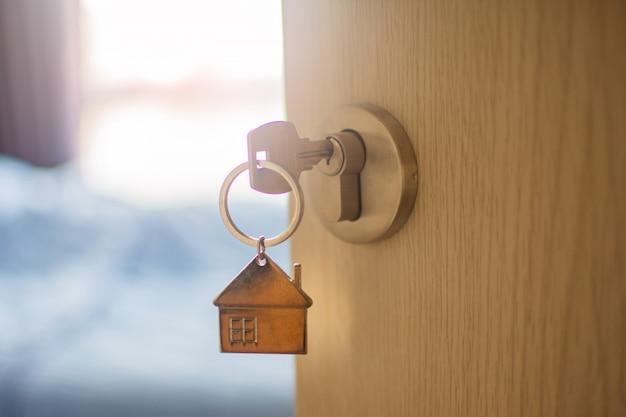 Sluit omhoog sleutel op de deur met ochtend lichte, persoonlijke lening. onderwerp is wazig.