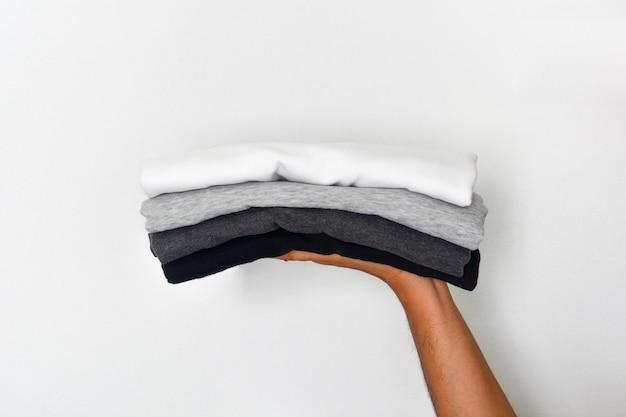 Sluit omhoog stapel van gevouwen zwarte, grijze en witte kleurentoon (zwart-wit) t-shirt in handen