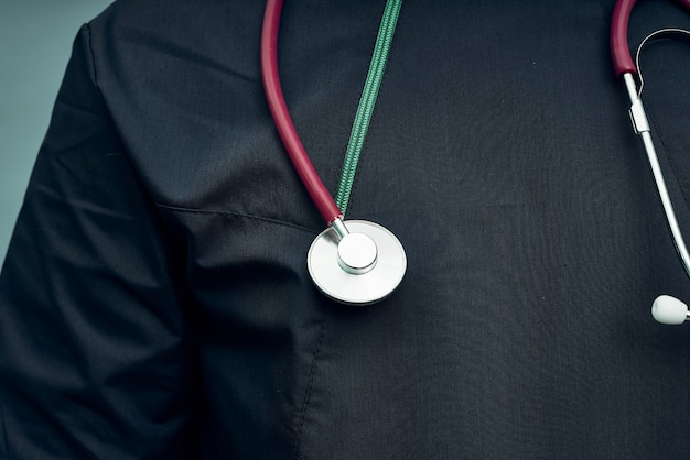 Sluit omhoog stethoscoop op donkerblauwe kleren van een arts