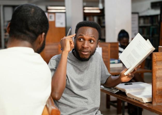 Sluit omhoog studenten met boek in bibliotheek