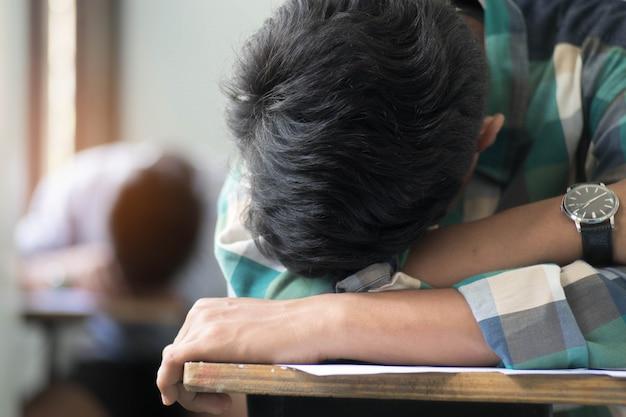 Sluit omhoog studentenslaap en het schrijven examen met spanning in klaslokaal.