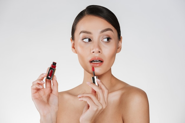 Sluit omhoog studioportret van donkerbruine vrouw met zachte huid die rode lipgloss toepast en weg kijkt, geïsoleerd over wit