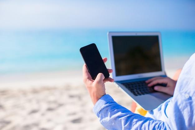 Sluit omhoog telefoon op computer bij het strand