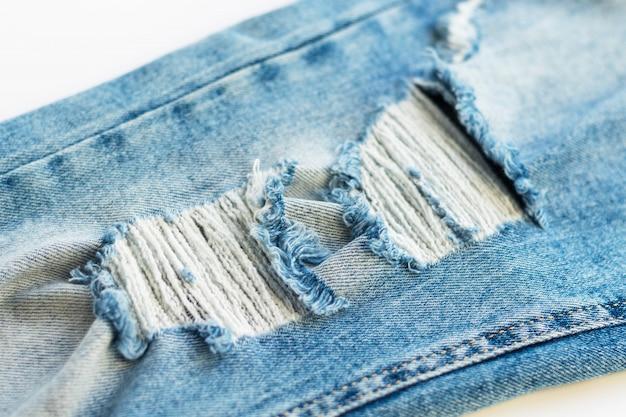 Sluit omhoog textuur van blauwe gescheurde jeans. trendy spijkerbroek met gescheurde knie. mode en stoffen thema.