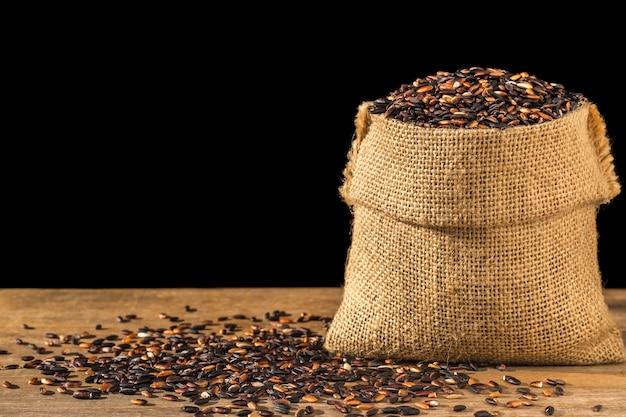 Sluit omhoog thaise zwarte kleverige rijst in kleine zak op houten lijst.