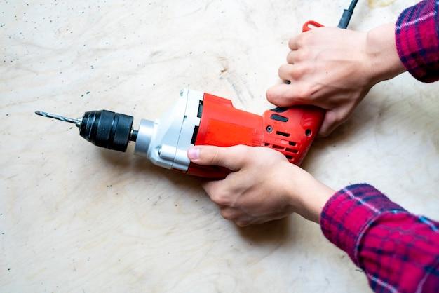 Sluit omhoog toevallige arbeider thuis houdend elektrische boor en herstelt meubilair f
