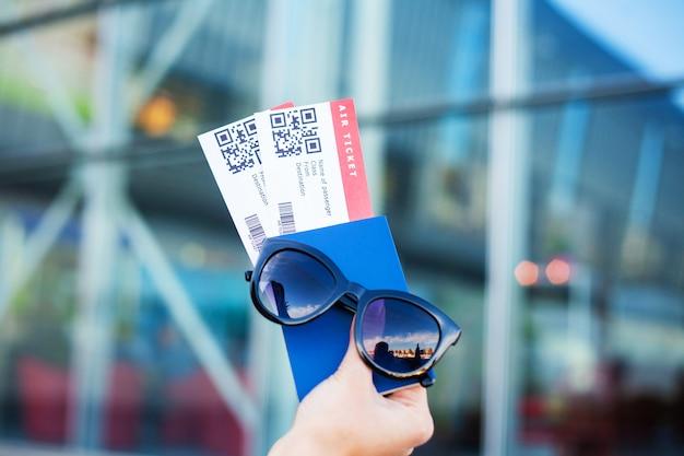 Sluit omhoog twee luchtkaartje in paspoort in het buitenland dichtbij luchthaven