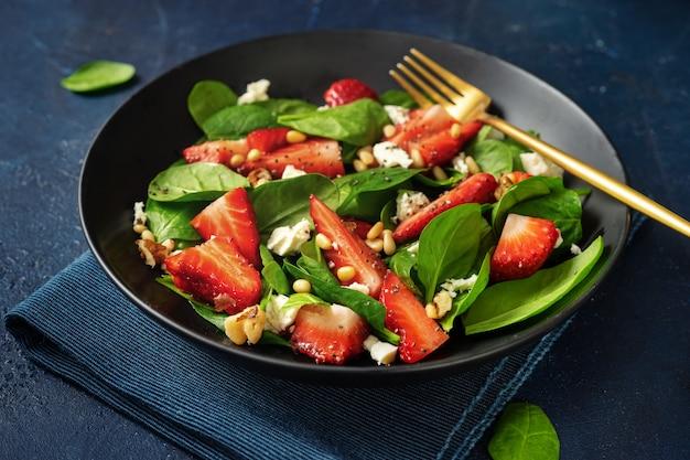 Sluit omhoog van aardbeisalade met spinazie, feta ans noten op blauwe achtergrond