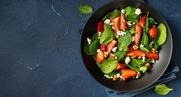 Sluit omhoog van aardbeisalade met spinazie, feta en noten op klassieke blauwe achtergrond