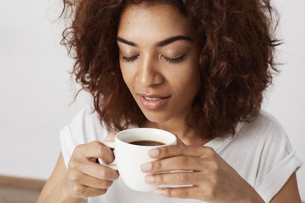 Sluit omhoog van afrikaanse de kop ruikende koffie van de meisjesholding met gesloten ogen.