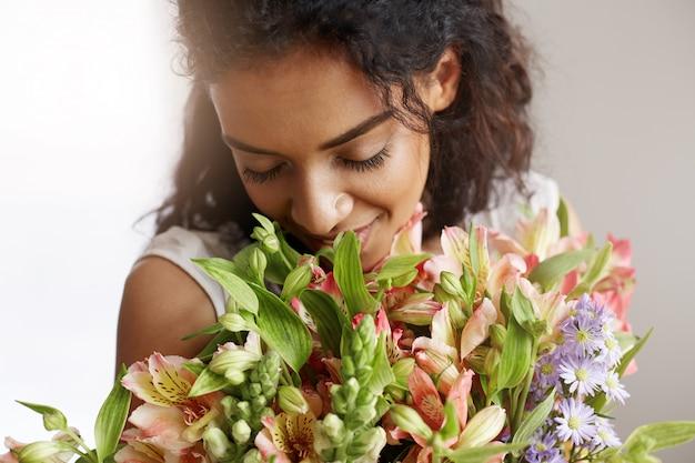 Sluit omhoog van afrikaanse vrouwenbloemist het glimlachen holding het snuiven boeket van alstroemerias. gesloten ogen.