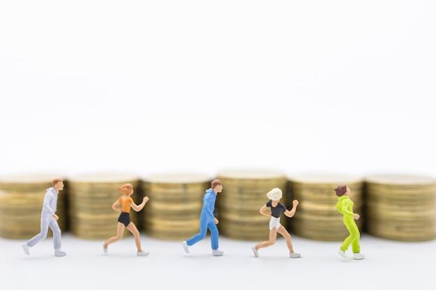 Sluit omhoog van agentgroep het miniatuur lopen voor rij van stapel muntstukken