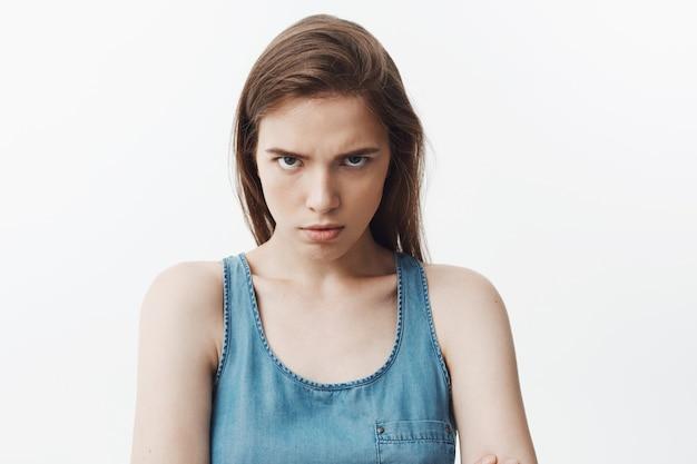 Sluit omhoog van agressieve aantrekkelijke jonge kaukasische vrouw met donker lang haar in blauw overhemd met boze gezichtsuitdrukking,