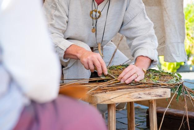 Sluit omhoog van ambachtsman die landelijke kleren dragen die rieten mand maken
