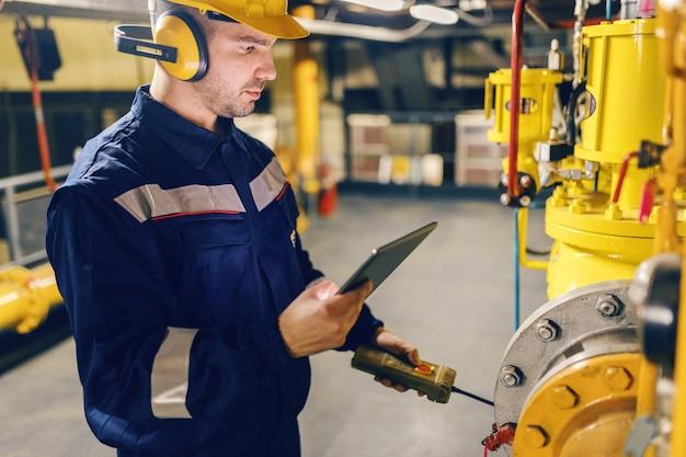 Sluit omhoog van arbeider in beschermend kostuum gebruikend tablet en dringende knoop terwijl status in hitteinstallatie.