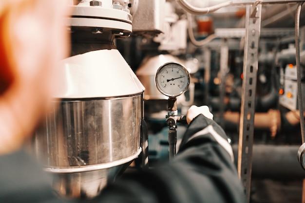 Sluit omhoog van arbeider in het aanpassen van de zware industrieinstallatie luchtdruk op boiler.
