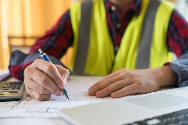 Sluit omhoog van architect die een bouwproject met laptop op werkplaats schetsen.
