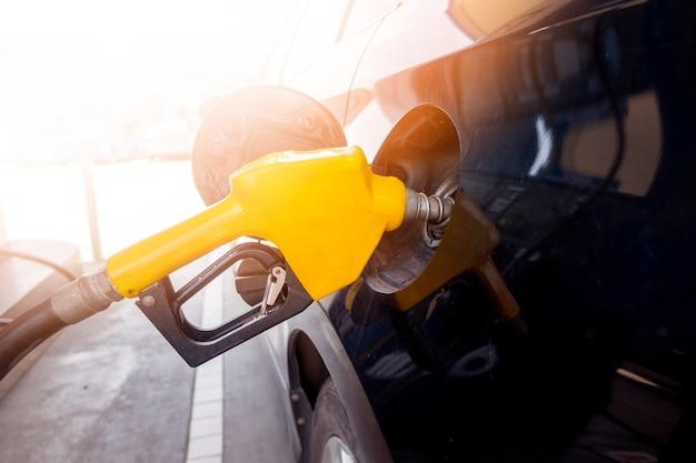 Sluit omhoog van auto vult oliebrandstof in benzinestation aan