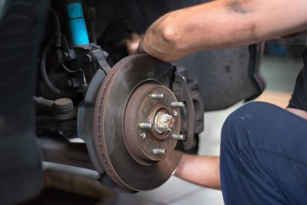 Sluit omhoog van autowerktuigkundige die remblokken herstellen
