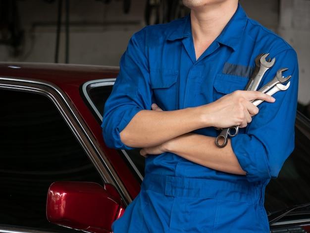 Sluit omhoog van autowerktuigkundige in eenvormige holdingshulpmiddelen of moersleutels in de garage.