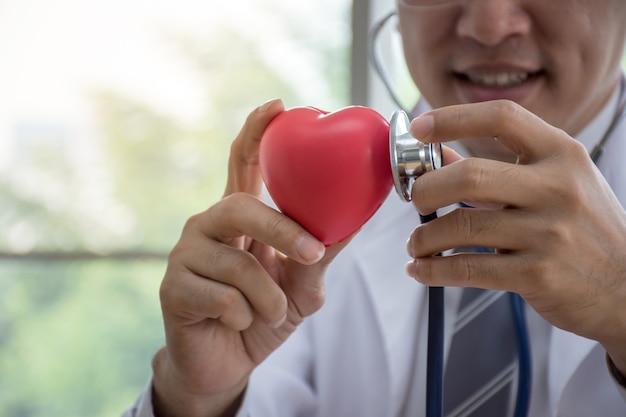 Sluit omhoog van aziatische arts met stethoscoop die rood hart onderzoekt