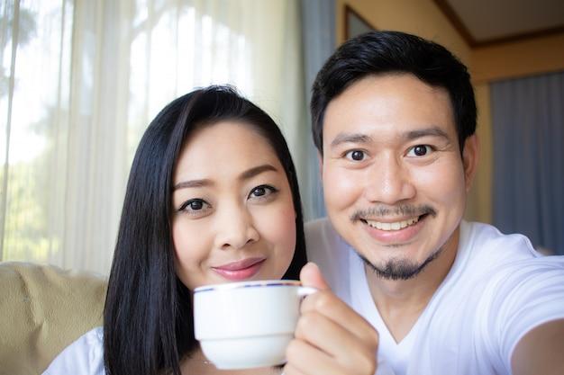 Sluit omhoog van aziatische paarminnaar drinkt hete koffie.