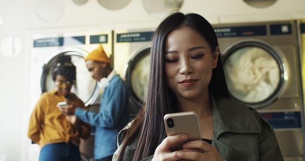 Sluit omhoog van aziatische vrij vrolijke vrouw die en bericht op smartphone in de ruimte van de wasserijdienst onttrekken tikken. mooi gelukkig meisje die op telefoon typen en op kleren wachten om in washuis schoon te worden.